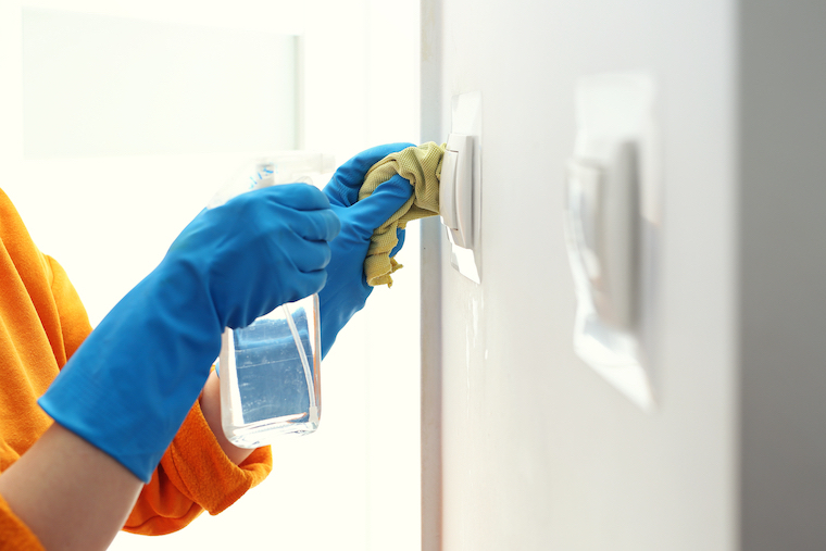 gloved hands cleaning light switch