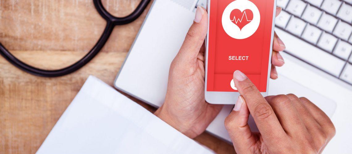 Medical,App,Against,Doctor,Using,Smartphone,On,Wooden,Desk